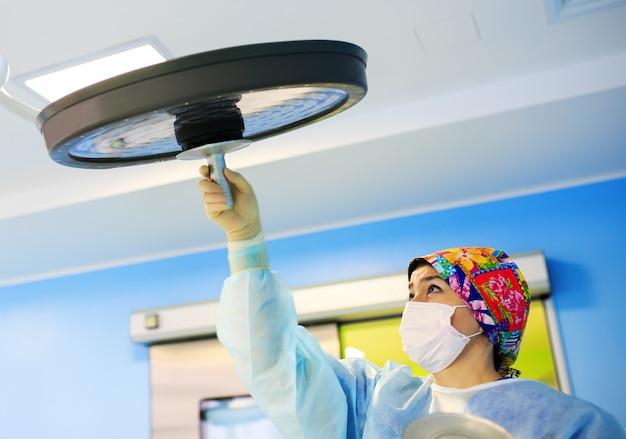 Хирург регулирует лампу в операционной