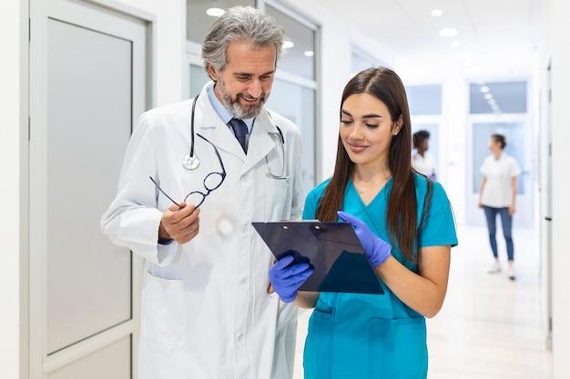 Хирург и женщина-врач идут по коридору больницы,
