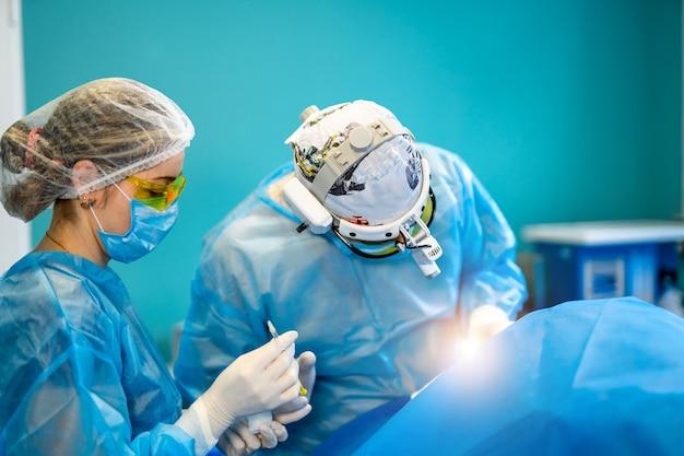 Хирург и его ассистент выполняют пластические операции в операционной больницы.