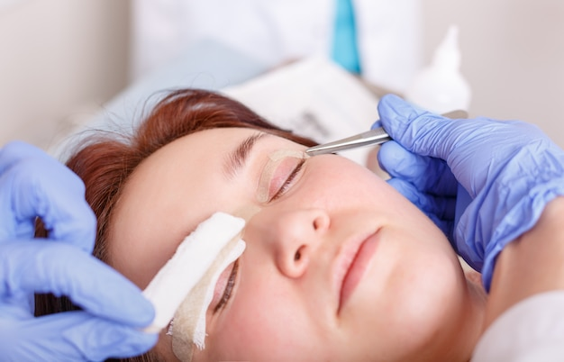 Surgeon applies a bandage to the female patient's eyelids after