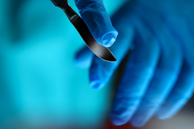 Surgeon arms in sterile uniform holding sharp knife