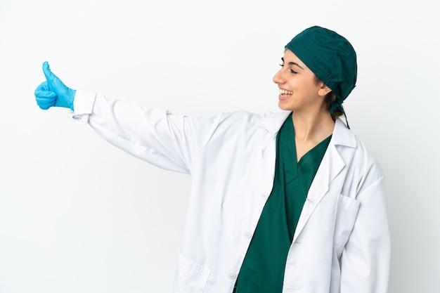親指を立てるジェスチャーを与える白い壁に分離された外科医白人女性