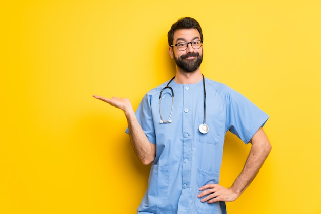 Surgeon doctor man holding copyspace imaginary on the palm to insert an ad