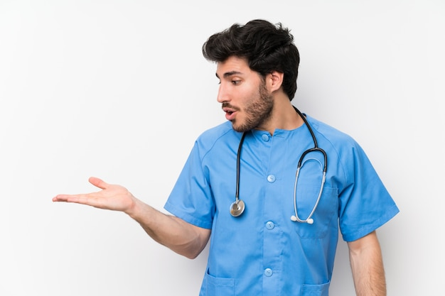 Surgeon doctor man over isolated white wall holding copyspace imaginary on the palm
