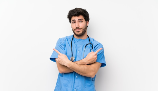 Surgeon doctor man over isolated white wall pointing to the laterals having doubts