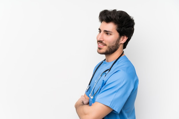 Surgeon doctor man over isolated white wall standing and looking to the side