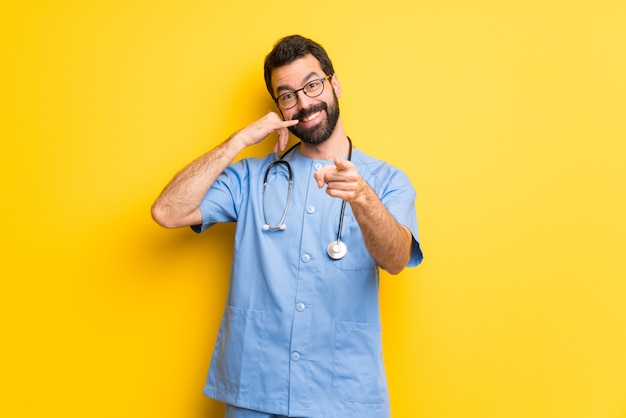 Surgeon doctor man making phone gesture and pointing front