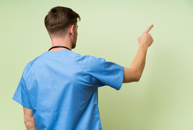 Surgeon doctor man pointing back with the index finger