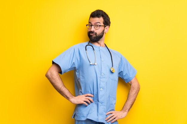 Surgeon doctor man posing with arms at hip and laughing looking to the front