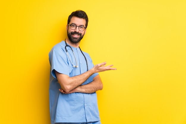 Surgeon doctor man presenting an idea while looking smiling towards
