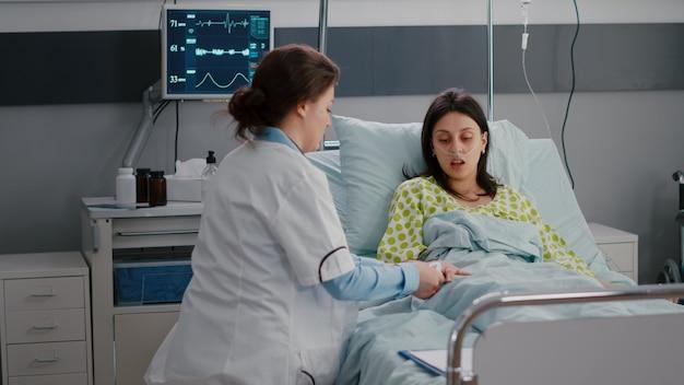 맥박 전문성을 검사하는 의료 산소 농도계를 넣어 병원 병동에서 심장학 약속 중에 입원 한 아픈 여자를 모니터링하는 외과 의사 의사