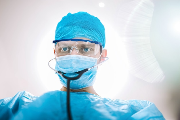 Surgeon doctor in the operating room looking at the camera
