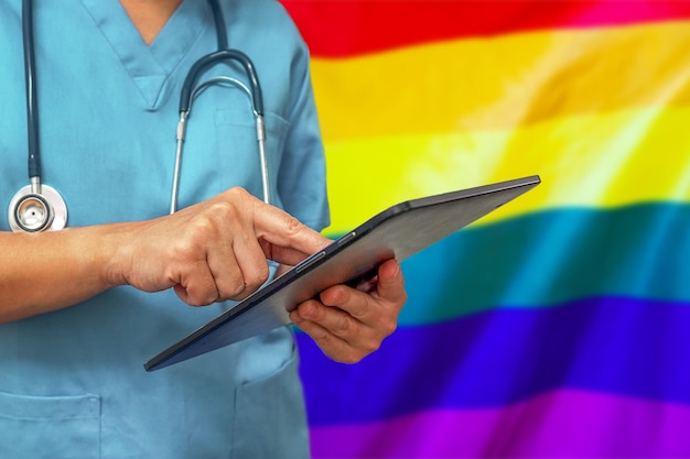 Surgeon or doctor using a digital tablet on the background of the lgbt gay flag