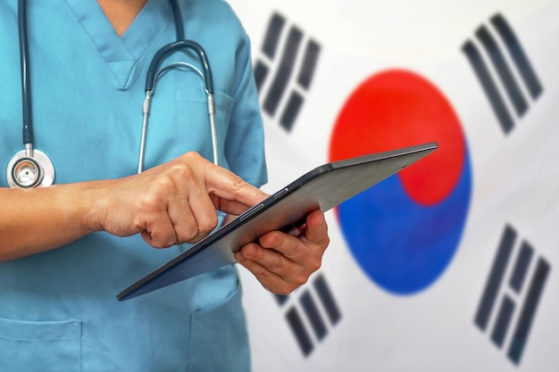 Surgeon or doctor using a digital tablet on the background of the south korea flag