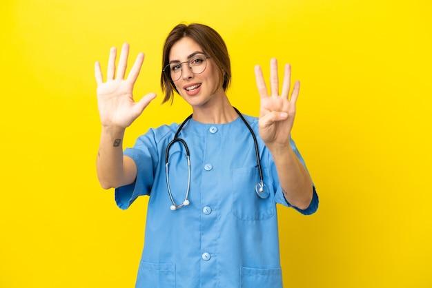 Женщина-врач-хирург изолирована на желтом фоне, считая девять пальцами
