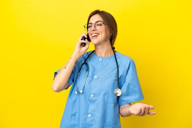 Женщина-хирург-врач изолирована на желтом фоне, разговаривая с кем-то по мобильному телефону