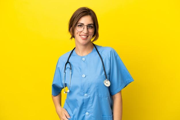 笑って黄色の背景に分離された外科医の医者の女性