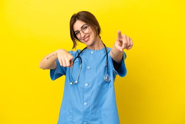 Женщина-врач-хирург, изолированная на желтом фоне, указывает пальцем на вас, улыбаясь