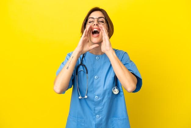 Женщина-врач-хирург, изолированные на желтом фоне, кричит и что-то объявляет