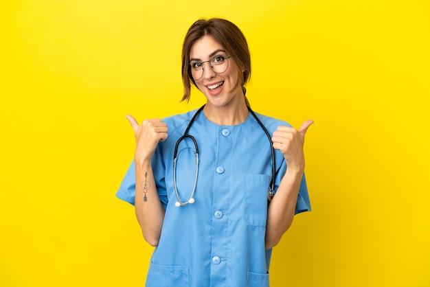 親指を立てるジェスチャーと笑顔で黄色の背景に分離された外科医の医者の女性