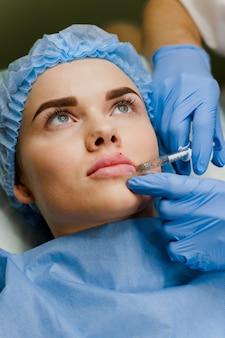 外科医は魅力的な女の子のために診療所でフィラーを使用してプラスチック手術の唇の増強を行います