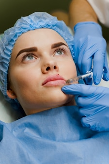 Surgeon does plastic opertation lips augmentation using filler in medical clinic for attractive girl