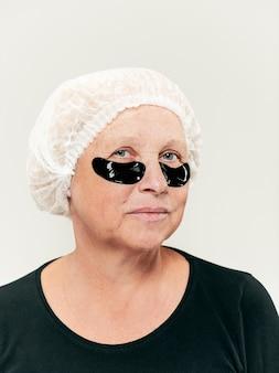 Chirurgo che fa il controllo della pelle sulla donna di mezza età prima della chirurgia plastica