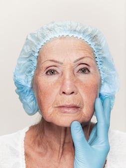 성형 수술 전에 중간 나이 여자 피부 검사를하고 외과 의사