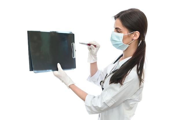 白い壁で患者のx線を検査する外科医