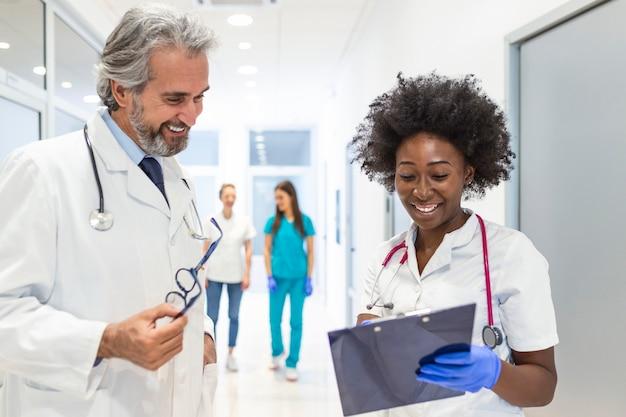 Surgeon and female doctor walk through hospital hallway,