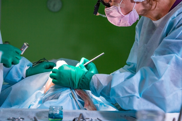 Surgeon and his assistant performing cosmetic surgery on nose in hospital operating room