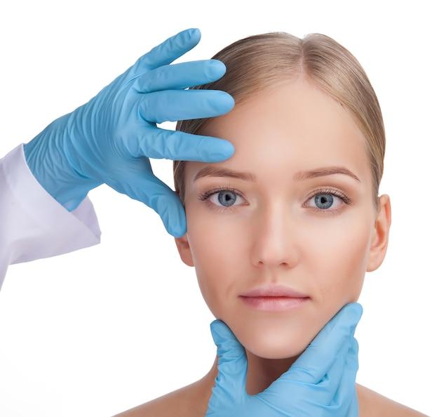 손, 근접 촬영으로 아름다운 여자의 얼굴을 만지고 파란색 장갑 외과 의사