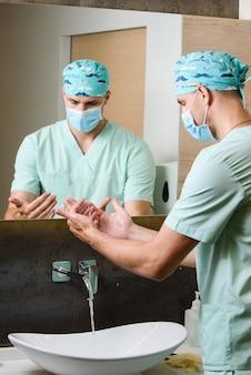 外科医は、水の流れの下で洗った後、彼の手の清潔さを見ます