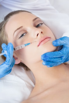 Surgeon making injection bove lips on pretty woman lying