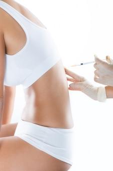Хирург делает инъекцию в женский организм. концепция нейронной терапии.