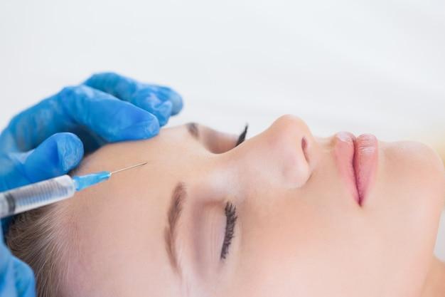 Хирург делает инъекции на естественной женщине, лежащей