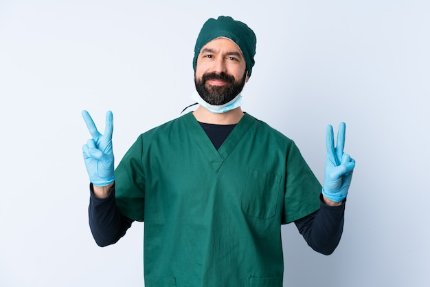 Surgeon man in green uniform over wall showing victory sign with both hands