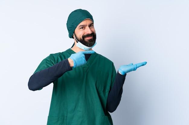 広告を挿入する手のひらに想像上のcopyspaceを保持している孤立した壁の上の緑の制服を着た外科医男
