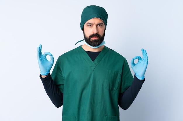 禅のポーズで孤立した壁の上の緑の制服を着た外科医男