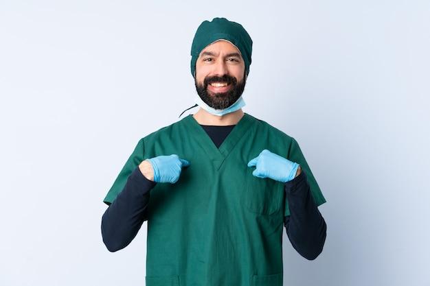 Хирург человек в зеленой форме на изолированной стене с удивлением выражением лица