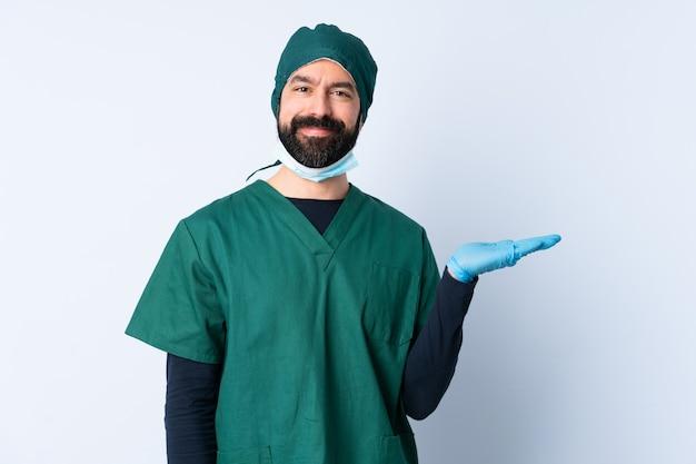 手のひらに空白を保持している壁を越えて緑の制服を着た外科医男