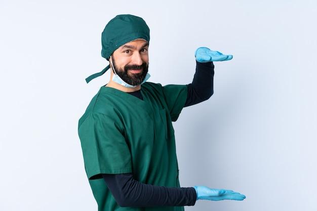 空白を保持している壁の上の緑の制服を着た外科医男