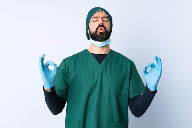 禅のポーズで壁を越えて緑の制服を着た外科医男