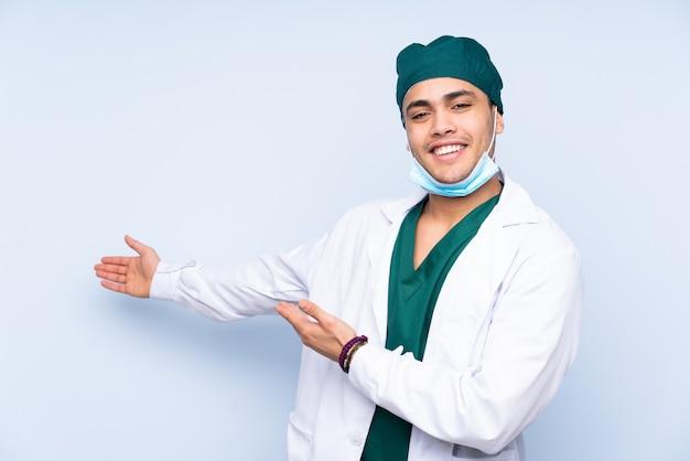 青い背景に分離された制服を着た外科医の男が来て招待するために手を横に伸ばします