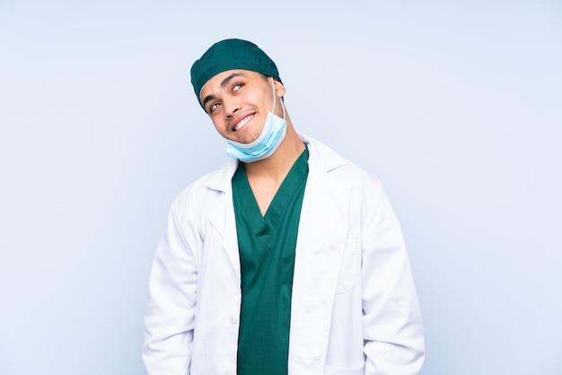 Человек хирурга с униформой, изолированные на синем фоне, смеясь и глядя вверх