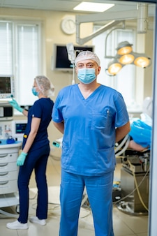 Surgeon in mask looking at camera. doctor in surgery office. team working on the background.
