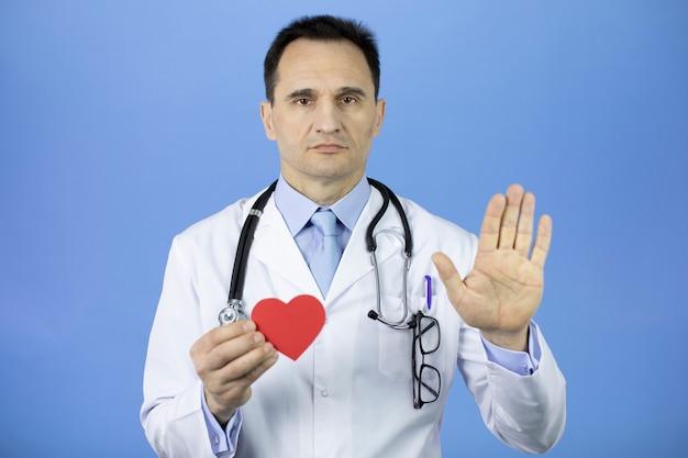 明るい青の外科医は左手に心臓を持ち、右手のひらを示しています