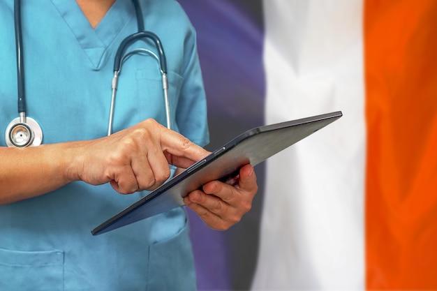 フランスの旗の背景にデジタルタブレットを使用して外科医または医師