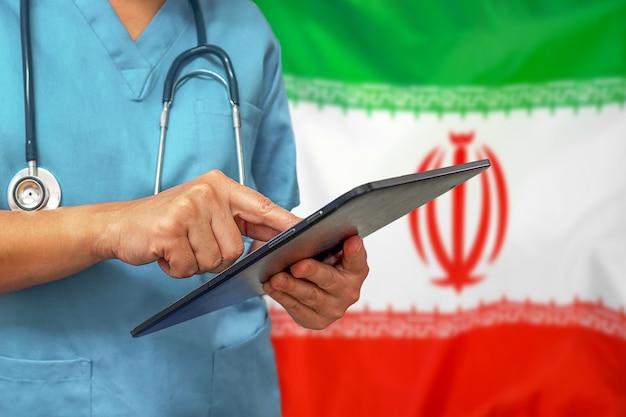 이란 국기의 배경에 디지털 태블릿을 사용하는 외과 의사 또는 의사