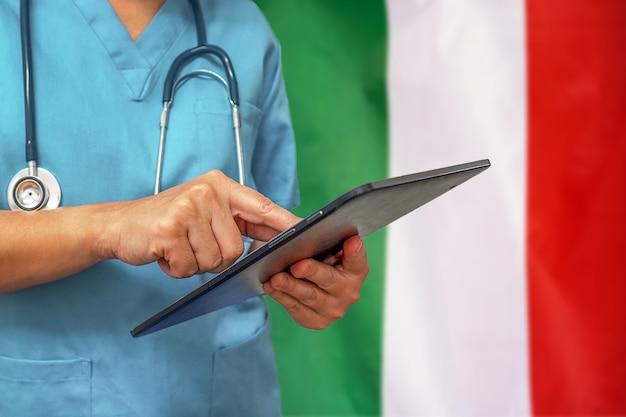Хирург или врач с помощью цифрового планшета на фоне флага италии